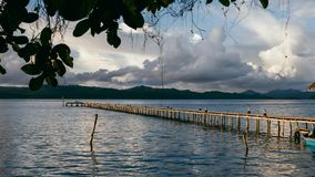 Cloudscape with wooden pier in kri island before tropical thunderstorm. Raja Ampat archipelago, West papua, Indonesia.  stock photo