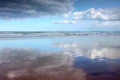 Cloudscapes reflected in wet sand on Makorori Beach, Gisborne, New Zealand. Cumulus cloud formations reflected in wet sand on Makorori Beach, Gisborne, New royalty free stock image