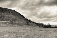 Cloudy afternoon in Czech central mountains landscape area near Mila hill in winter without snow in december 2017 in sepia styliza Royalty Free Stock Photos