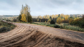 Cloudy autumn forest with a road. Cloud weather Stock Photos