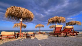 Cloudy beach at dusk. Sunshades and lounges on a cloudy beach at dusk Stock Image