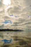 Cloudy beach. Mirror image of cloudy beach shore Stock Photography