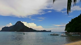Cloudy beach and mountains. Cloudy beach with boats and mountains in the distance stock footage