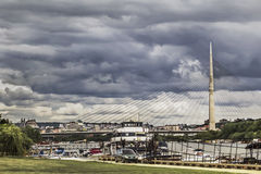 Cloudy Belgrade Skyline With The Bridge Over Ada. Panoramic photograph of cloudy Belgrade skyline with boats shelter on Sava river and the Bridge Over Ada pylon Royalty Free Stock Photography
