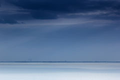Cloudy blue minimalist seascape. Deserted space. Horizon line. Stock Photos