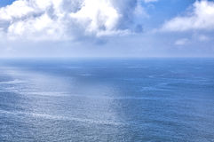 Cloudy blue sky above a blue surface Stock Photography