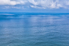Cloudy blue sky above a blue surface Royalty Free Stock Photography