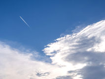Cloudy blue sky with contrail Stock Photography