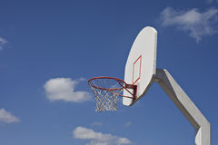 Cloudy blue sky frames retro basketball goal. Cloudy blue sky frames old orange and white basketball goal royalty free stock photo