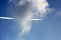 Cloudy blue sky with jet trail Stock Photos