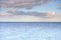 Cloudy blue sky leaving for horizon blue surface sea. Cloudy blue sky leaving for horizon above a blue surface of the sea stock image
