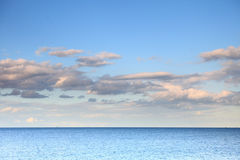 Cloudy blue sky leaving for horizon blue surface sea Royalty Free Stock Image