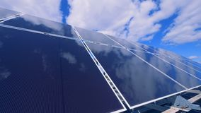 Cloudy blue sky is mirroring in the solar array. 4K stock video footage