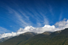 Cloudy blue sky and mountains Stock Images