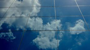 Cloudy blue sky reflection. Blue sky reflection shot from low angle glass building stock images