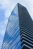 Cloudy blue sky reflection skyscraper glass exterior trees frami Stock Image