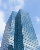 Cloudy blue sky reflection skyscraper glass exterior trees frami Royalty Free Stock Image