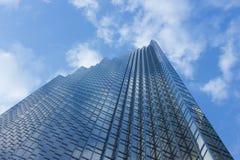 Cloudy blue sky reflection skyscraper glass exterior trees frami Stock Images