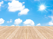 Cloudy blue sky with sun beam and wood floor Stock Image