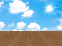 Cloudy blue sky with sun beam and wood floor Stock Photo
