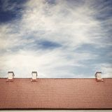 Cloudy blue sky and tiled roof top Royalty Free Stock Photo