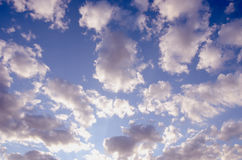 Cloudy blue spring sky sun-lit background Stock Images