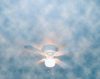 Cloudy and Breezy. Ceiling fan emerging from the 'clouds stock images