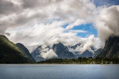 Cloudy with a chance of ... beautiful photo!. Panoramic View of Mountain peaks and glacier engulfed in the clouds in the background and Milford Sound Marina in stock photography