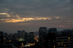 Cloudy city sunset. Sunset on cloudy day in lighted streets Stock Photography