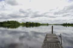 Cloudy Creek. Cloudy gray sky over a slow moving creek with old wooden dock Stock Images