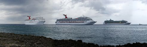Cloudy Cruising Day. Panoramic view of three cruise liners drifting by Grand Cayman island on a cloudy day stock image