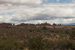 Cloudy day at Arches National Park. The desert plants in the field around Arches National Park, fluffy white clouds, and the unique rock figures of the park Stock Photography