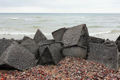 Cloudy day on the beach with concrete fortifications near the se Stock Images