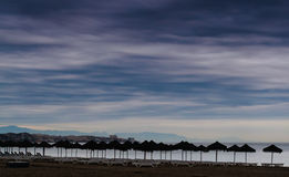 Cloudy Day At The Beach. The rain is coming at Fuengirola, Spain. The sunny beach is soon turning into a mud puddle. I wonder if those umbrellas are study enough royalty free stock image