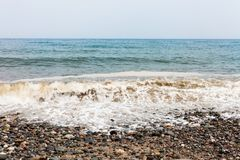 Cloudy day on the beach side with waves hitting seashore. Sea foam on the waves. Rocky beach with colorful stones. Blue sky withou royalty free stock photo