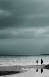 Cloudy Day at the Beach. Two walkers silhouetted against bright water with dark clouds above them Royalty Free Stock Photo