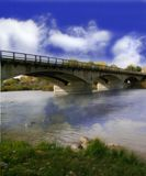A Cloudy Day bridge. A grassy river bank with a blue sky and puffy white clouds Royalty Free Stock Photos