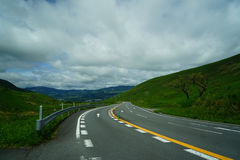 On cloudy day curved road trip after raining through local green mountain scenic route during springtime with road sign lines. Yufuin, Japan Stock Photos