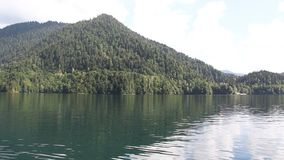 Cloudy day on lake Ritsa in Abkhazia. Forested mountains and white clouds reflected in the water stock footage