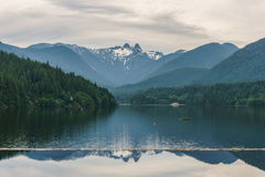 Cloudy day on mountain lake and green forest Royalty Free Stock Image