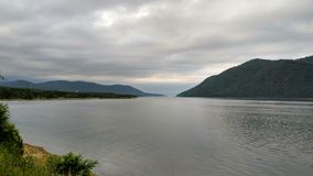 Cloudy day on the river / lake - coast, water surface shore royalty free stock image