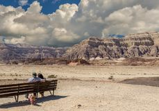 Cloudy day in Timna geological park, couple of seniors are looking at mountains. View on the valley of geological Timna park and dry riverbed. It is located 25 Stock Photos