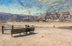Cloudy day in Timna geological park, couple of seniors are looking at mountains. View on the valley of geological Timna park and dry riverbed. It is located 25 Royalty Free Stock Photography