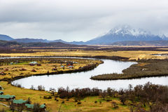 Cloudy day in Torres del Paine National park, Chilean Patagonia. A nice river with a mountain full of snow in the background Stock Images