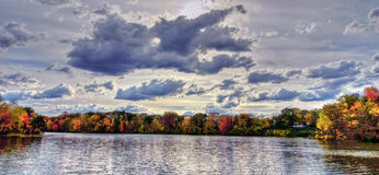 Cloudy Days. Cloudy skies alongside a peaceful lake during the calm season of Autumn Stock Photo