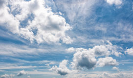 Cloudy dynamic formation on a blue summer sky. Dramatic weather background with beautiful cloud arrangement Royalty Free Stock Images