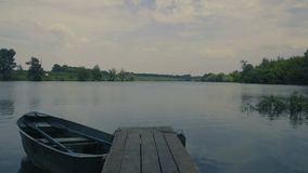 Cloudy evening on pond. Fishing boat near pier in cloudy evening on pond stock footage