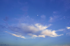 Cloudy evening sky and the moon. Cloudy evening sky and the moon in soft sun shine Royalty Free Stock Photos