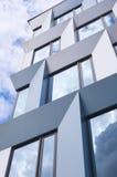 Cloudy facade. Modern office building facade mirroring clouds stock images