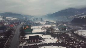 Cloudy foggy day in early spring. Aerial rural view of misty village and road. stock video